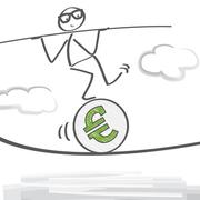 Figur balanciert auf einem Euro.